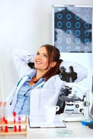 Medical doctor woman sitting at office table and relaxing  photo