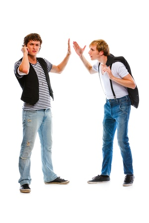 discontented: Young modern man with mobile showing wait gesture his indignant friend