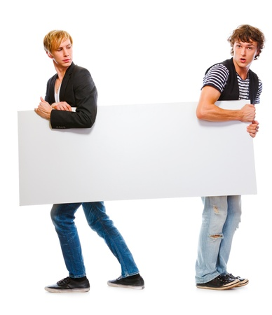 Two modern teenagers holding blank billboard. Isolated on white  photo