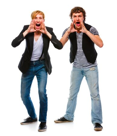 Two cheerful  young men shouting through megaphone shaped hands  Stock Photo