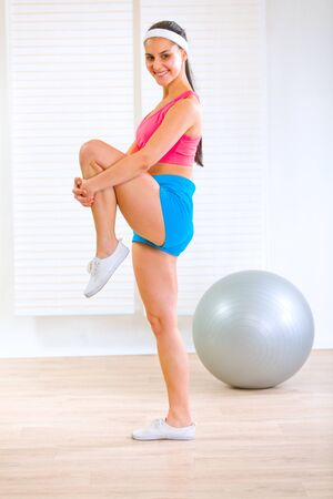 Happy fitness girl doing stretching exercises at living room  photo