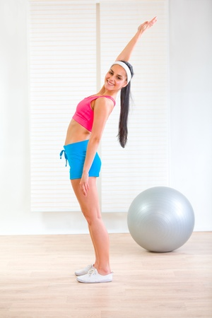Full length portrait of happy fit girl doing exercises at living room  photo