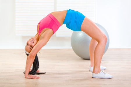 Fitness girl doing bridge exercise at living room  photo