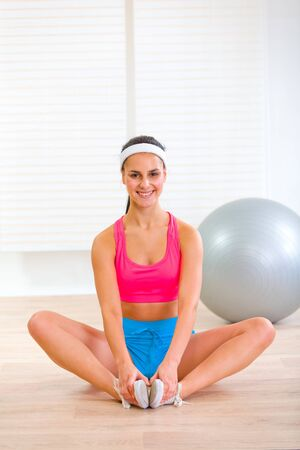 Smiling girl in sportswear sitting in yoga pose at living room  photo