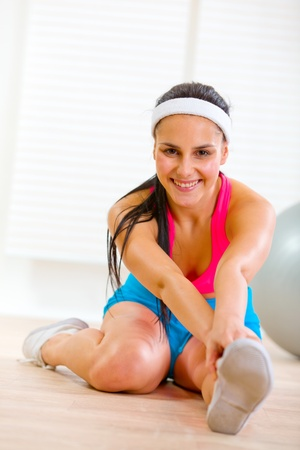 Smiling fitness woman making gymnastics exercise at living room  photo