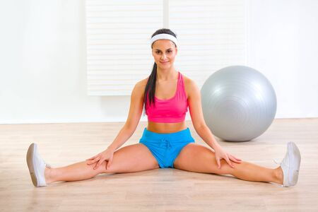 Happy flexible fitness girl stretching legs on floor at living room   photo