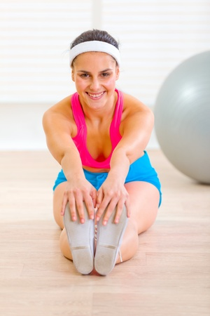 Happy young female doing exercises on floor at living room  photo