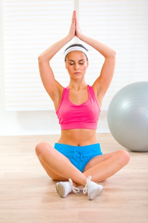 Concentrated beautiful woman doing yoga exercises on floor at living room  photo
