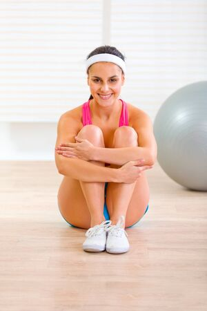 Smiling fit girl in sportswear sitting on floor at living room  photo