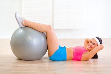 Smiling fit girl doing abdominal crunch on fitness ball at living room  photo