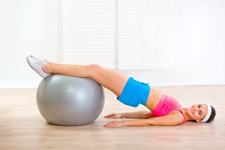 Smiling young woman doing abdominal crunch on fitness ball at living room  photo