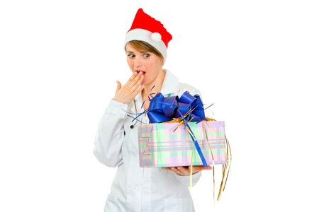 heal new year: Surprised medical doctor woman in Santa hat looking on present box isolated on white
