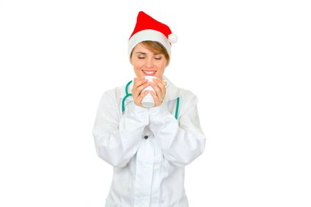 heal new year: Happy medical female doctor in Santa hat enjoying cup of hot coffee isolated on white