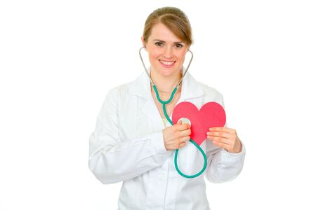 Happy medical female doctor holding stethoscope on paper heart isolated on white