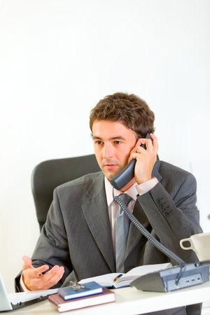 Serious businessman sitting at office desk and speaking phone  photo