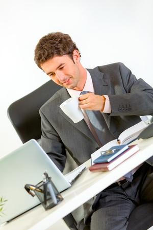 Happy businessman drinking coffee and looking in laptop  photo