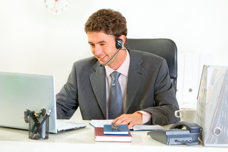 Smiling manager with headset looking in laptop  photo