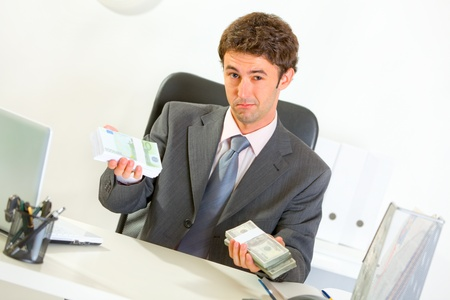 money packs: Authoritative modern businessman sitting at office desk and offering money packs