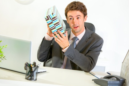 interrogatively: Interested modern businessman shaking present box trying to guess whats inside