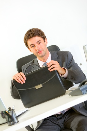 Confident modern businessman sitting at office desk with briefcase   photo