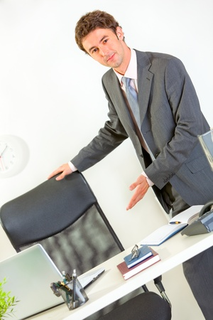 Modern businessman offering to seat at desk  photo