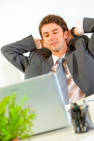 Pleased modern businessman relaxing on office armchair and looking in laptop  photo