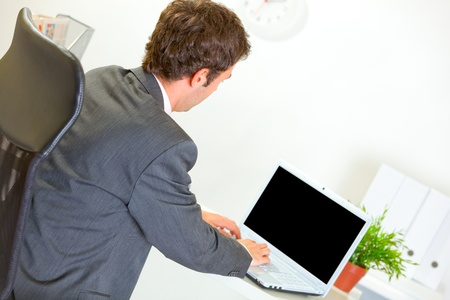 Modern businessman working on laptop at office   photo