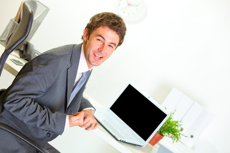 Pleased modern businessman  sitting at office desk and  showing yes gesture  photo