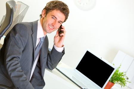 Successful modern businessman in office making phone call  photo