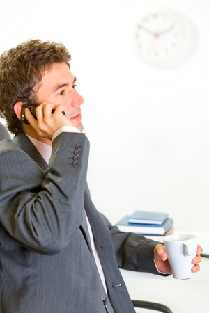Serious modern businessman in office talking mobile  photo