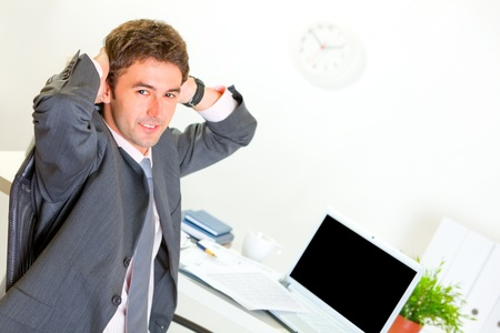Pleased modern businessman relaxing on armchair at office desk  photo
