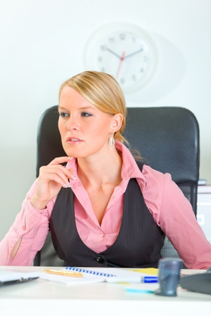 sagacious: Thoughtful modern business woman sitting at office desk