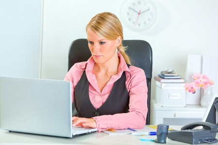 sagacious: Business woman working on laptop at office desk  Stock Photo
