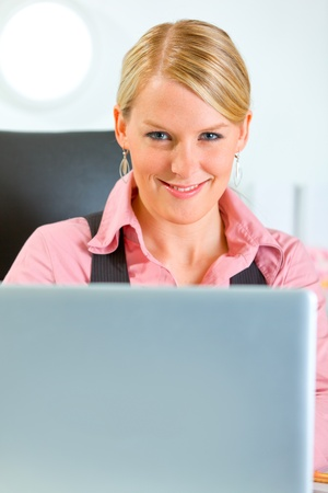 Happy modern business woman working on laptop at office  photo