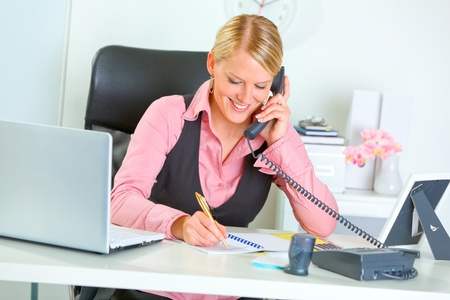business woman phone: Smiling modern business woman talking phone and writing at notepad  Stock Photo