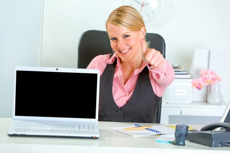 Smiling modern business woman showing laptops blank screen and thumbs up  photo