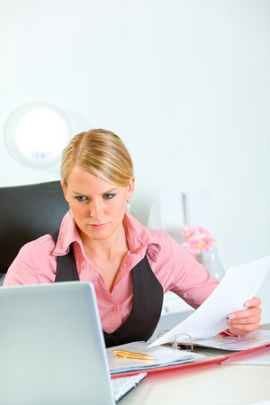 Serious business woman holding document and looking in laptop  photo