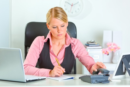 Working at office business woman picking up phone  photo
