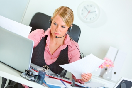 Confused modern female manager with headset at working place
