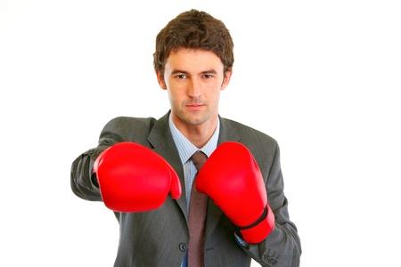 authoritative: Authoritative modern businessman in boxing gloves punching  isolated on white