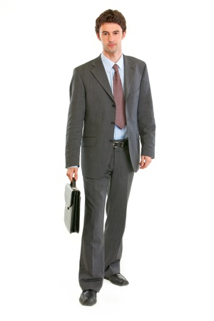 certitude: Confident modern businessman with suitcase making step  isolated on white