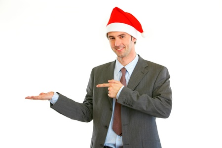 Smiling modern businessman in Santa Hat pointing on empty hand isolated on white  photo