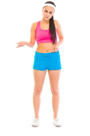 disgruntled: Unhappy girl in sportswear checking body fat isolated on white