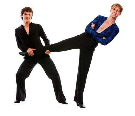 merry dancers: Ballroom male dancer holding leg of his funny posing friend