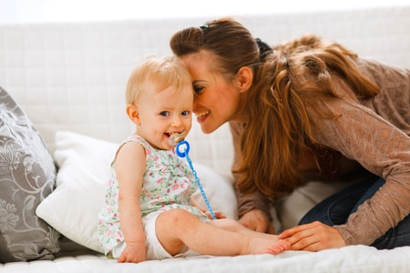 Adorable baby with soother and young mother playing on divan at home