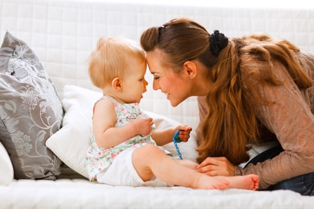 Cute baby with soother and young mom playing on divan at home
