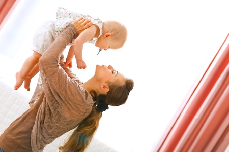 Young mama playing with baby by rising her up at home Stock Photo - 11151265