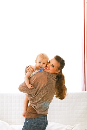 Young mom showing her baby something by pointing in camera