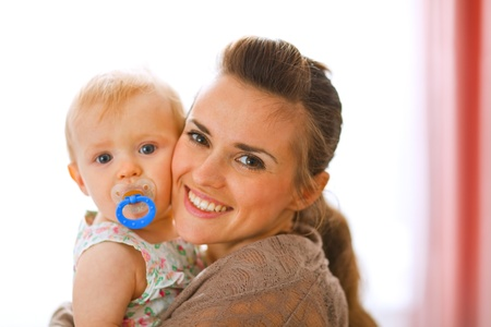 gleeful: Portrait of beautiful young mother with her baby at home  Stock Photo