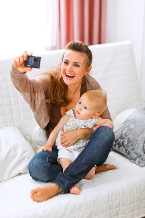 Beautiful young mom making photos with her lovely baby at home Stock Photo - 11151244
